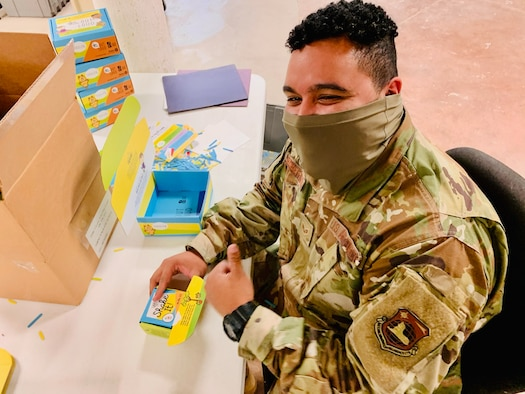 "Senior Airman Kwame Robertson of Wright-Patterson Air Force Base's National Air and Space Intelligence Center builds ""Love Them Out Loud"" kits during the Dec. 18 volunteer event benefiting the Dayton Metro Library and early childhood literacy."