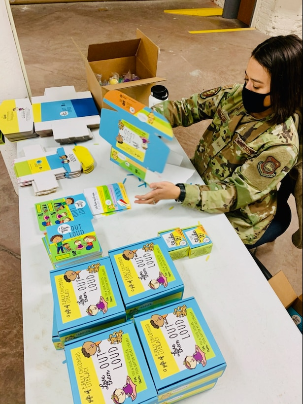 """Airman 1st Class Miranda Hutton of Wright-Patterson Air Force Base's National Air and Space Intelligence Center puts together """"Love Them Out Loud"""" kits during the Dec. 18 volunteer event benefiting the Dayton Metro Library and early childhood literacy."""