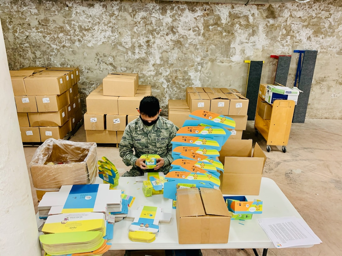 "Airman 1st Class Jasper Kaamino of Wright-Patterson Air Force Base's National Air and Space Intelligence Center assembles ""Love Them Out Loud"" kits during the Dec. 18 volunteer event benefiting the Dayton Metro Library and early childhood literacy."