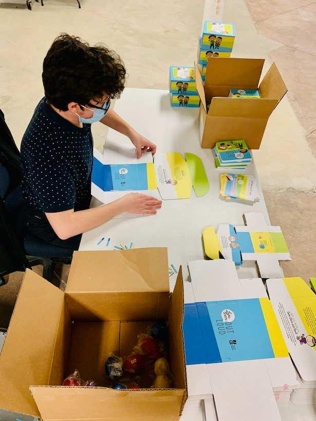 """Diego Quevedo of Wright-Patterson Air Force Base's National Air and Space Intelligence Center builds """"Love Them Out Loud"""" kits during the Dec. 18 volunteer event benefiting the Dayton Metro Library and early childhood literacy."""