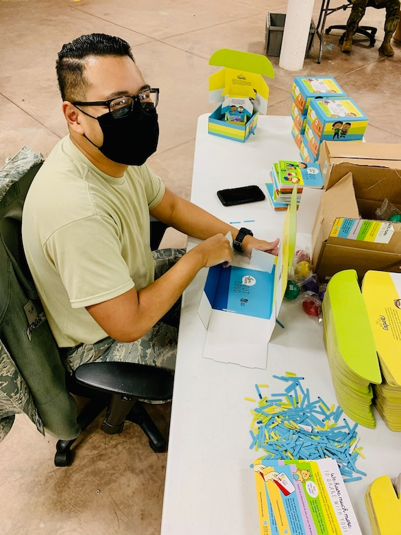 "Senior Airman Ariel Guzman of Wright-Patterson Air Force Base's National Air and Space Intelligence Center assembles ""Love Them Out Loud"" kits during the Dec. 18 volunteer event benefiting the Dayton Metro Library and early childhood literacy."