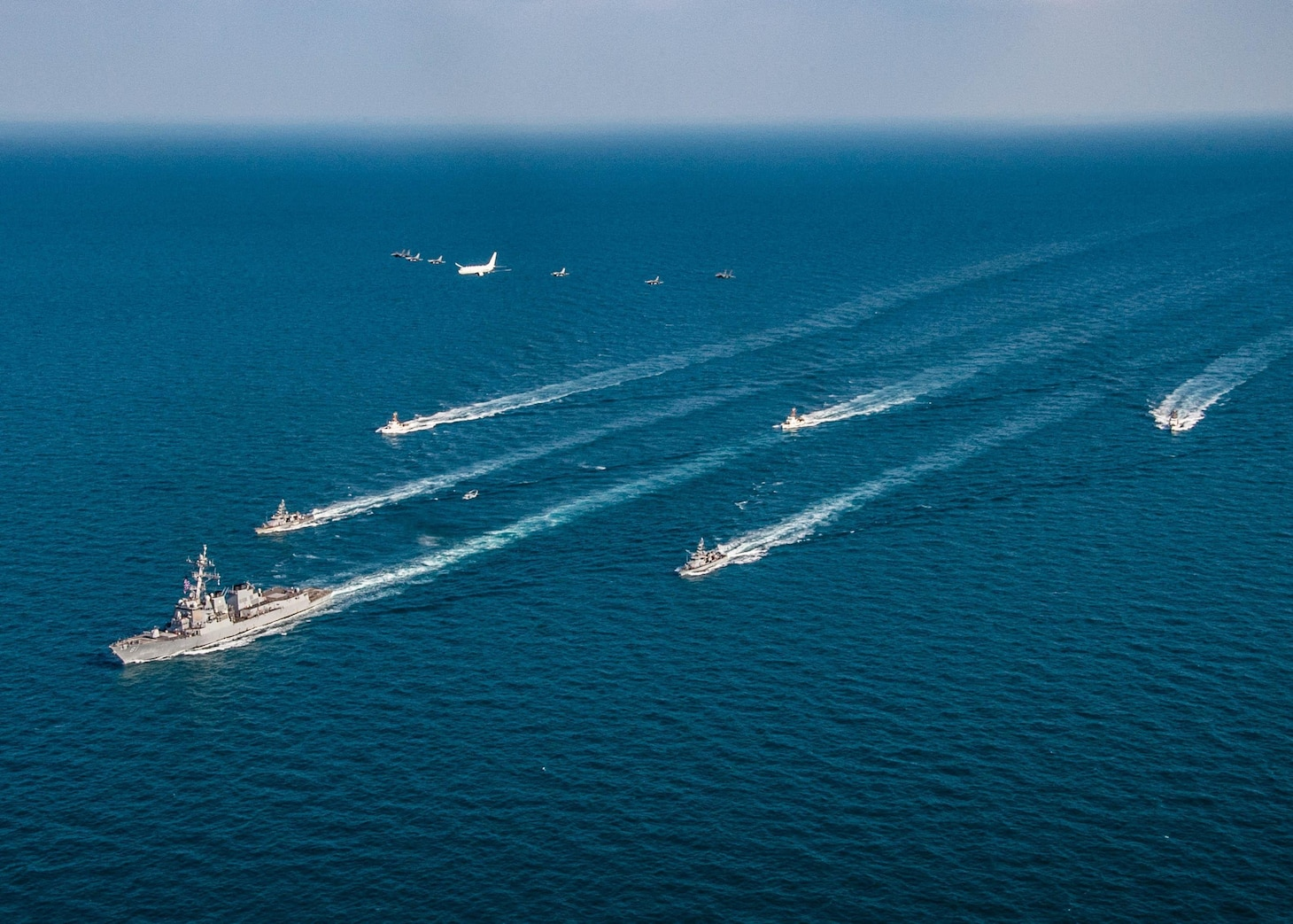 The guided-missile destroyer USS Winston S. Churchill (DDG 81), left to right, the Navy patrol coastal ships USS Firebolt (PC 10), USS Squall (PC 7), center, and the Coast Guard patrol boats USCGC Maui (WPB 1304), USCGC Monomoy (WPB 1326) and USCGC Wrangell (WPB 1322) transit the Arabian Gulf with Royal Saudi Air Force F-15SA fighter jets, U.S. Air Force F-16 Fighting Falcon fighter jets, a U.S. Navy MH-60R Sea Hawk helicopter and a U.S. Navy P-8A Poseidon aircraft during the joint and combined air operations in support of maritime surface warfare (AOMSW) exercise in the Arabian Gulf, Dec. 17. Combined integration operations between joint U.S. forces are regularly held to maintain interoperability and the capability to counter threats posed in the maritime domain, ensuring freedom of navigation and free flow of commerce throughout the region's heavily trafficked waterways.