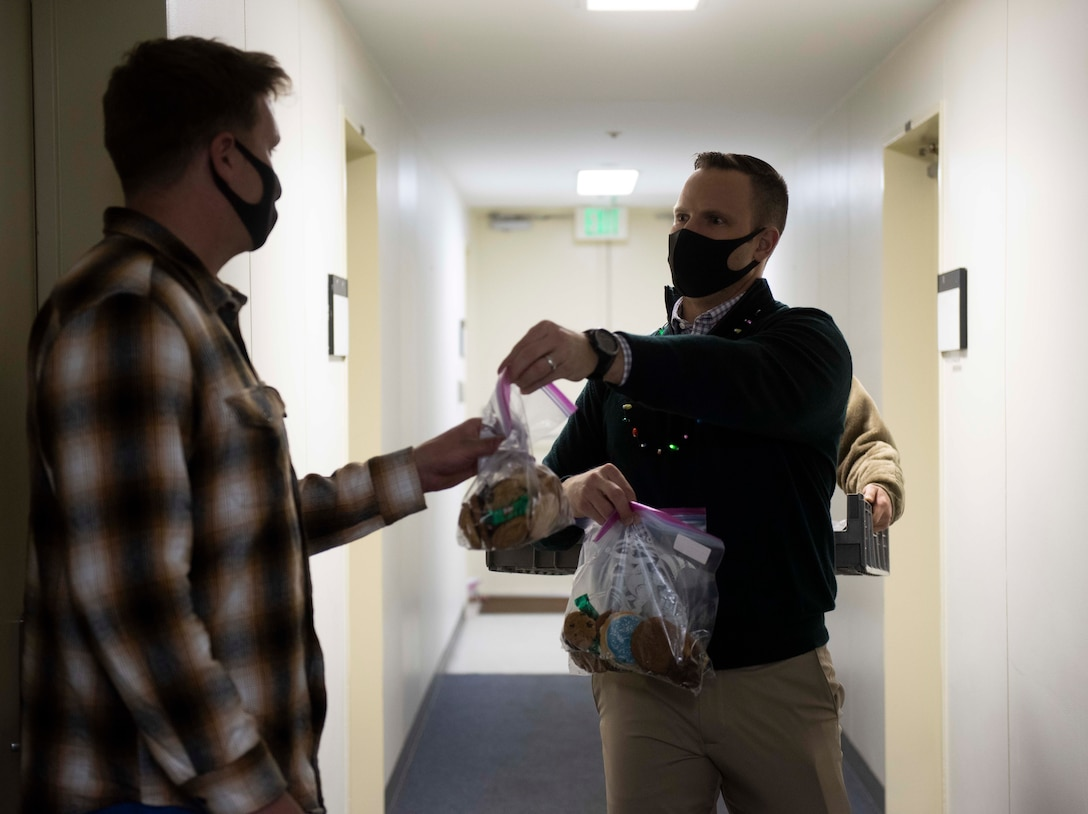 Lt. Col. Stephen Maddox, 374th Communications Squadron commander, drops off a bag of cookies to an Airman during the 2020 Team Yokota Cookie Crunch event on Yokota Air Base, Japan, Dec. 18, 2020. More than 15,600 cookies were donated, bagged and distributed to single U.S. and Japan Air Self-Defense Force Airmen during the holiday season. (U.S. Air Force photo by Airman 1st Class Hannah Bean)