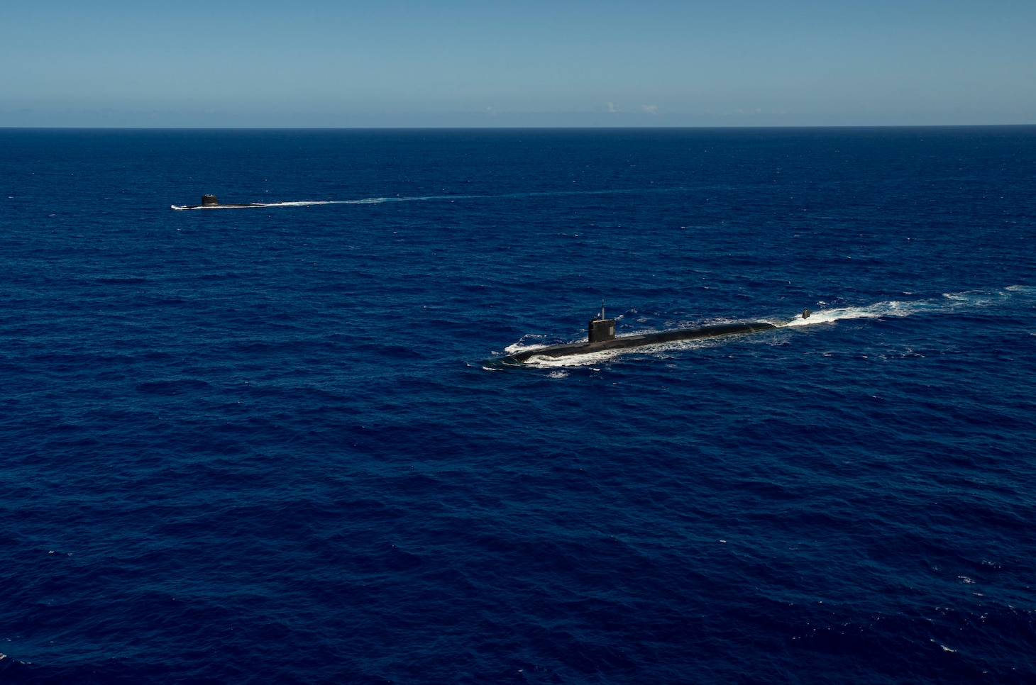 WATERS OFF GUAM (Dec. 11, 2020) The Los Angeles-class fast-attack submarine USS Asheville (SSN 758), right, and the French Navy Rubis-class nuclear powered submarine (SSN) Émeraude steam in formation off the coast of Guam during a photo exercise. Asheville and Émeraude practiced high-end maritime skills in a multitude of disciplines designed to enhance interoperability between maritime forces. Asheville is one of four forward-deployed submarines assigned to Commander, Submarine Squadron 15. (U.S. Navy photo by Mass Communication Specialist 2nd Class Kelsey J. Hockenberger)