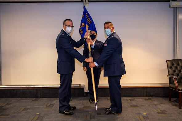 Col. Gregory Buchanan, 911th Airlift Wing Operations Group commander, passes a guidon to incoming 911th Aeromedical Staging Squadron Commander Lt. Col. Gregory S. Sell during an assumption of command ceremony at the Pittsburgh International Airport Air Reserve Station, Pennsylvania, Nov. 8, 2020.