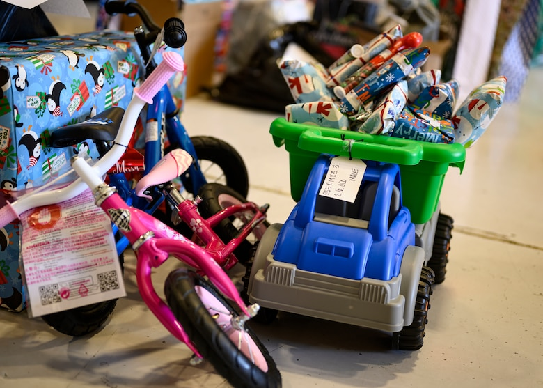 a pink bike and blue toy dump truck loaded with wrapped gifts