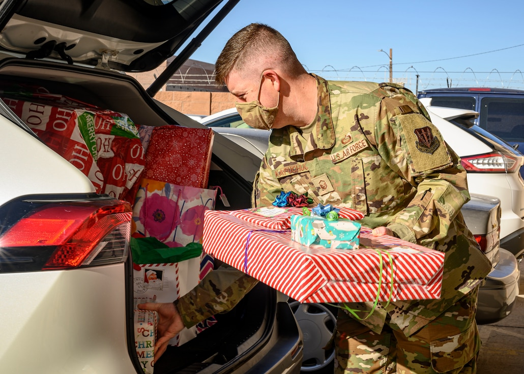 A first sergeant loads wrapped presents into a car