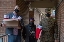 U.S. Marine Corps Cpl. Spencer Sargeant, an intel analyst, left, Lance Cpl. Jazzmyne Meadows, a logistic embarkation specialist, middle, and Pfc. Brendan Flatley, a Marine Air Ground Task Force planner with Headquarters and Service Battalion, U.S. Marine Corps Forces Command, Fleet Marine Force Atlantic, deliver stuffed stockings to Marines living in the barracks at Camp Elmore, Norfolk, Virginia, Dec. 21, 2020. The Marines on Camp Elmore received holiday stockings from the Daughters of the American Revolution association and from the families of service members. (U.S. Marine Corps photos by Cpl. Danielle Abshire/released)