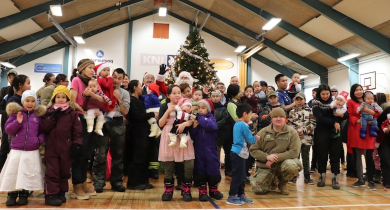 Members from Thule Air Base bring Christmas gifts to local Greenlandic children.