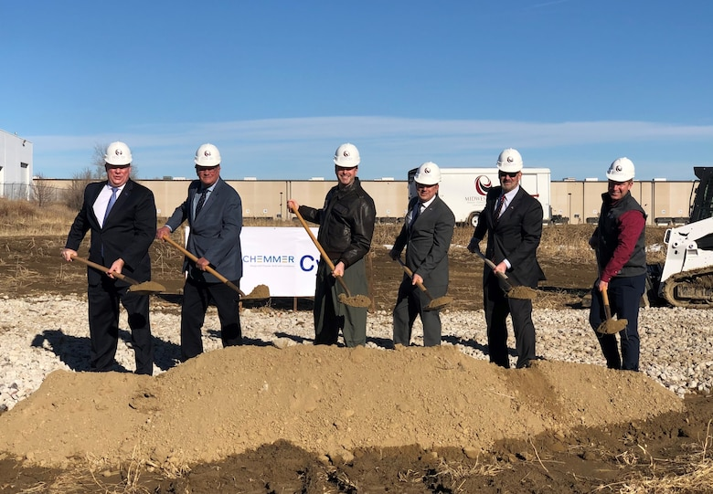 Six men stand in a line in front of a pile of dirt with shovels at a ground-breaking ceremony