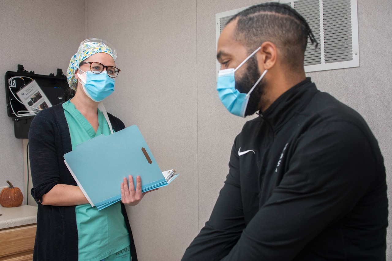 A nurse interacts with an assistant.