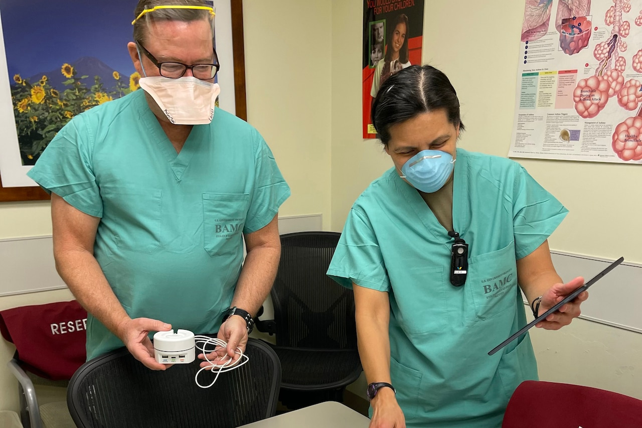 Two health care workers handle equipment.