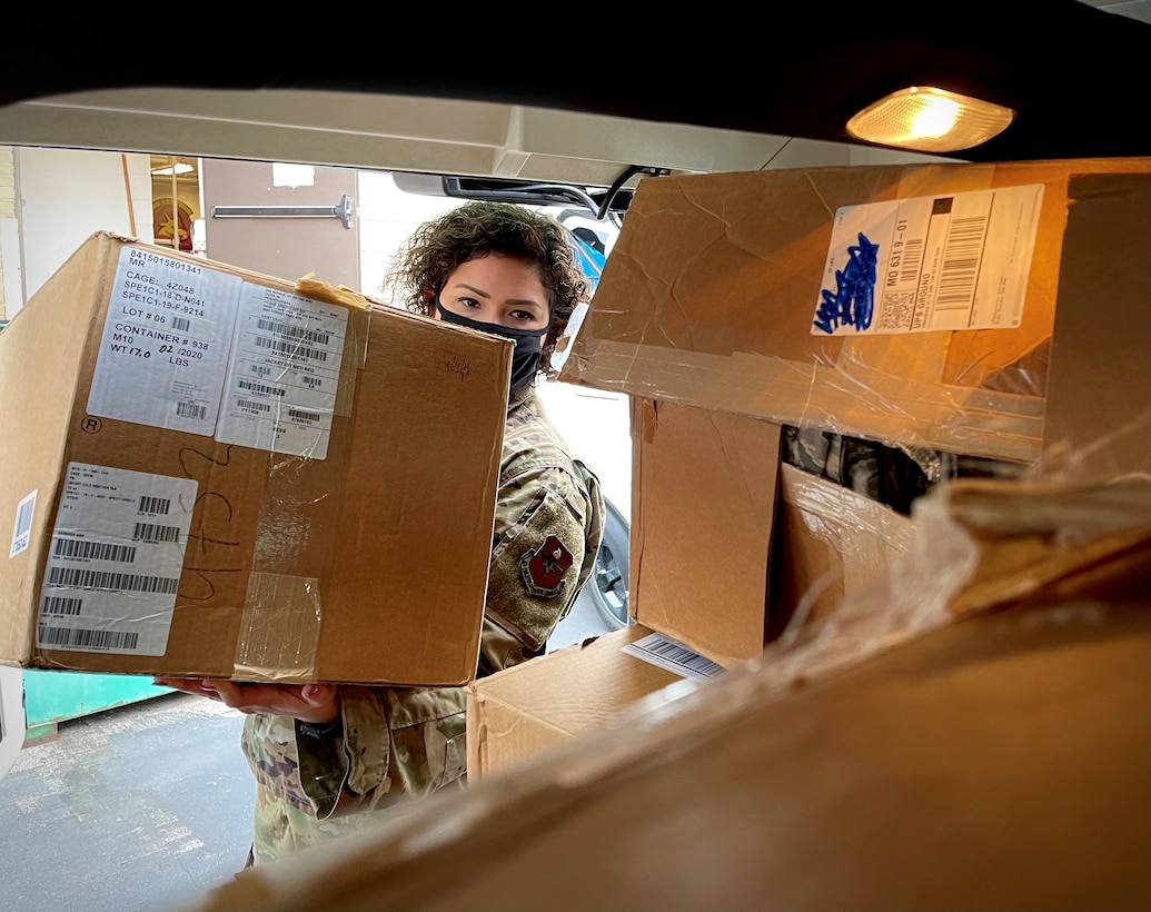 U.S. Air Force Master Sgt. Coralys Ross, noncommissioned officer in charge of Air Force ROTC Detachment 207, loads boxes filled with Airman Battle Uniform items into a car during a donation event at Saint Louis University, St. Louis, Missouri Dec. 18, 2020. The donation to a local Air Force Junior ROTC detachment, valued at more than $20,000, resulted from the transition of Air Force ROTC cadets to the Operational Camouflage Pattern uniform during the Fall 2020 academic semester.