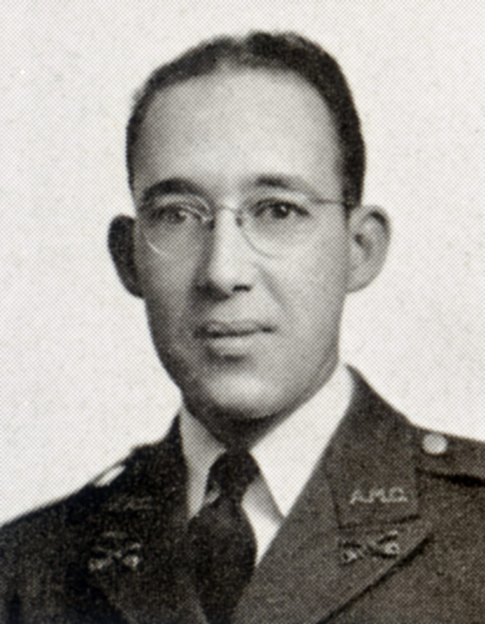 A man in glasses and a uniform looks at the camera.