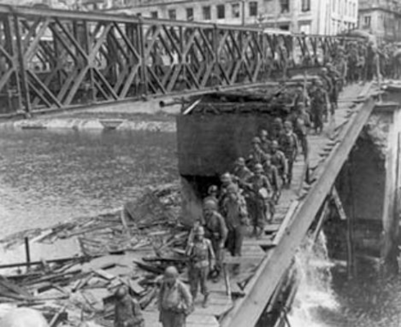 Dozens of soldiers march across a foot bridge over a river.