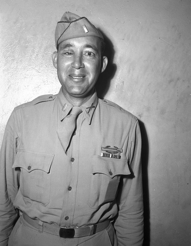 A man in dress uniform and cap smiles for the camera.