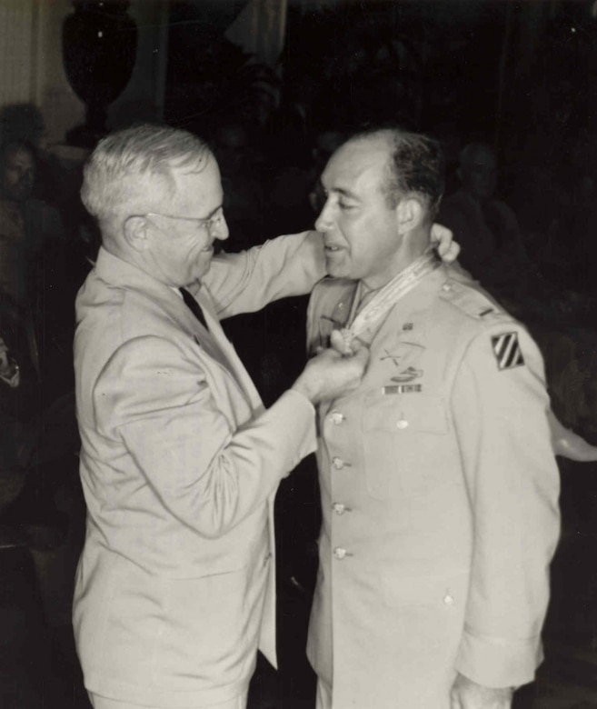 A man puts a medal around another man's neck.