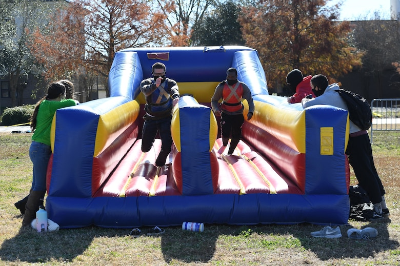 U.S. Air Force Airman 1st Class Tavis Pascual and Airman Joseph Delijah, 336th Training Squadron, participate in an inflatable race at Keesler Air Force Base, Mississippi, Dec. 18, 2020. The 81st Training Group held various events for Airmen to participate in throughout the holidays, to include ice skating, inflatables, a scavenger hunt and a bubble ball soccer tournament. (U.S. Air Force photo by Kemberly Groue)
