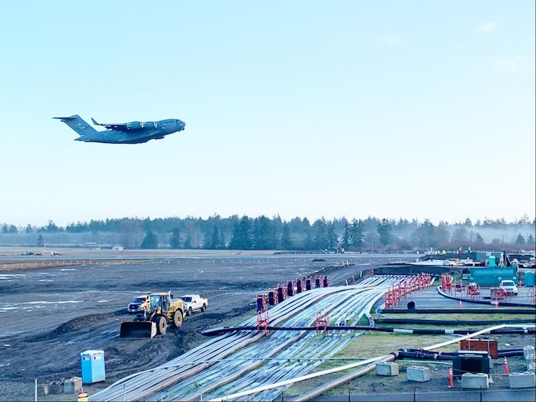 A McChord C-17 Globemaster III flies over the newly constructed airfield bridge to reopen the full runway at McChord Field at about 10 a.m. Dec. 22. (Photo Credit: Joe Piek, JBLM Public Affairs)