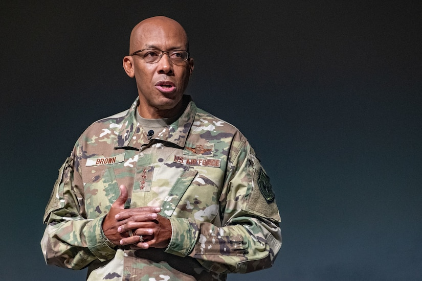 A man in a military uniform appears on a stage.