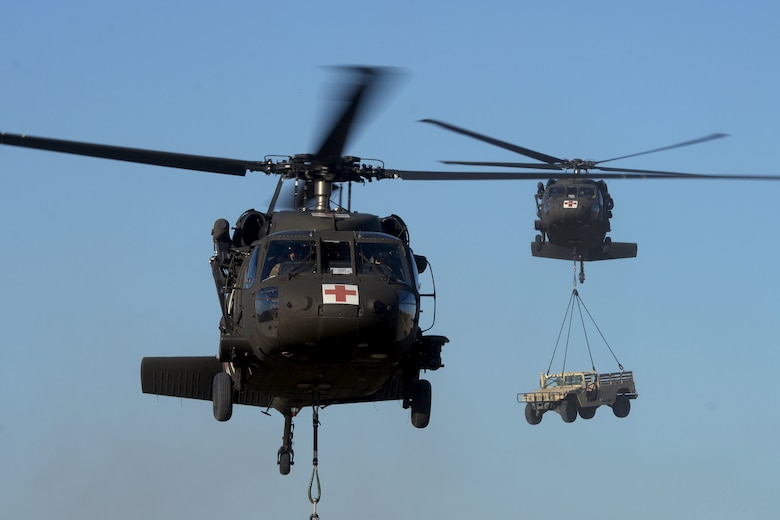Two UH-60 Black Hawk helicopters carry sling loaded cargo to predetermined destinations during Operation Nightstorm Dec. 15, 2020, at Joint Base San Antonio-Chapman Training Annex, Texas. (U.S. Air Force photo by Tech. Sgt. Samantha Mathison)