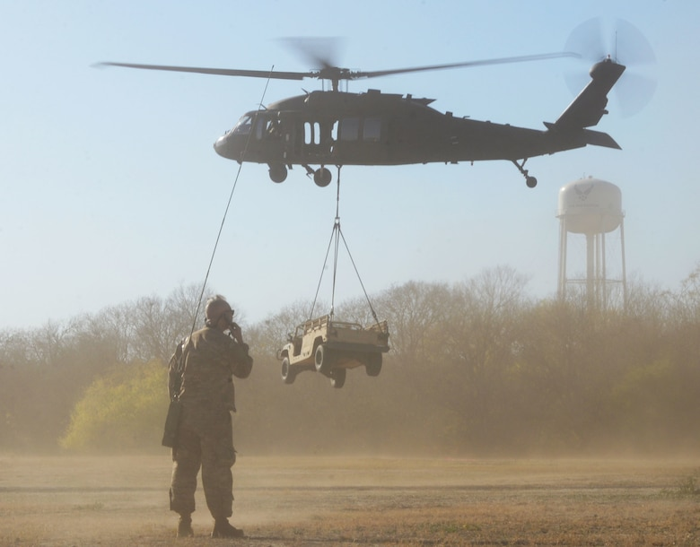Col. Kjäll Gopaul, Air Education and Training command pathfinder, watchs as a high mobility multi-purpose wheeled vehicled is lifted off the ground by a UH-60 Black Hawk helicopter Dec. 15, 2020, at Joint Base San Antonio-Chapman Training Annex, Texas. (U.S. Air Force photo by Tech. Sgt. Samantha Mathison)