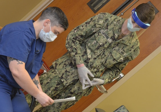 Lt. Cmdr. Alexandra Perry, a physician who works in the intensive care unit at Naval Hospital Jacksonville, reviews a COVID-19 vaccine information sheet prior to receiving the hospital's first dose of the new vaccine on Dec. 16.