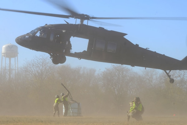 Operation Nightstorm team members work together to attach a sling load to a UH-60 Black Hawk helicopter Dec. 15, 2020, at Joint Base San Antonio-Chapman Training Annex, Texas. (U.S. Air Force photo by Tech. Sgt. Samantha Mathison)