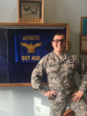"""Technical Sgt. Vince Boven poses beside the Air Force ROTC Detachment 400 guidon at Michigan Technological University in Houghton, Michigan. """"Boven is an amazing noncommissioned officer and will be an outstanding officer,"""" said Lt. Col. Joseph Pulliam, AFROTC Detachment 400 commander."""