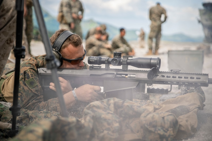 A Marine lies prone while preparing to fire a rifle.