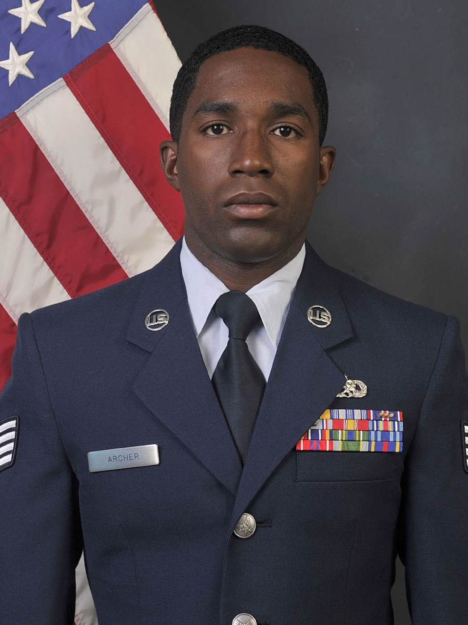 A man wearing dress blues looks at the camera.