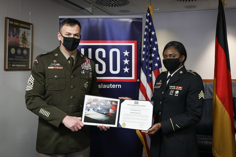 Two service members in masks hold up an award certificate in front of a USO sign.