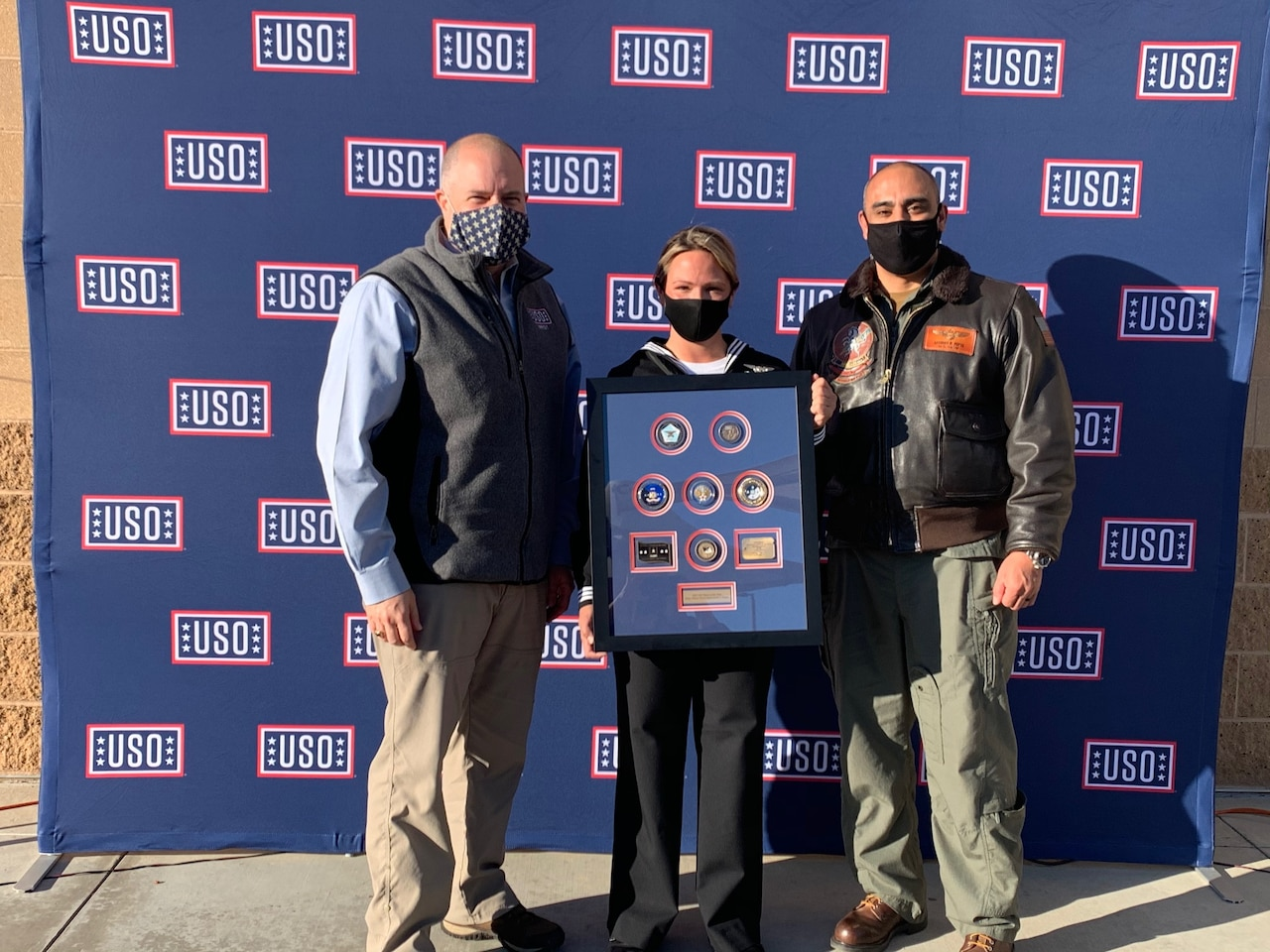 A sailor standing between two men holds a plaque. A USO backdrop is behind them.