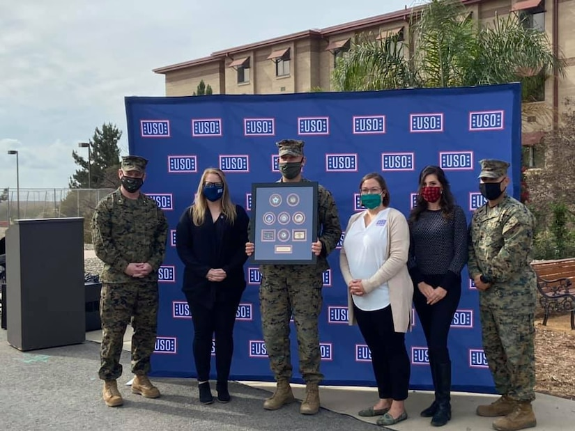 A Marine holding a plaque poses with two fellow Marines and three women in front of a USO backdrop.