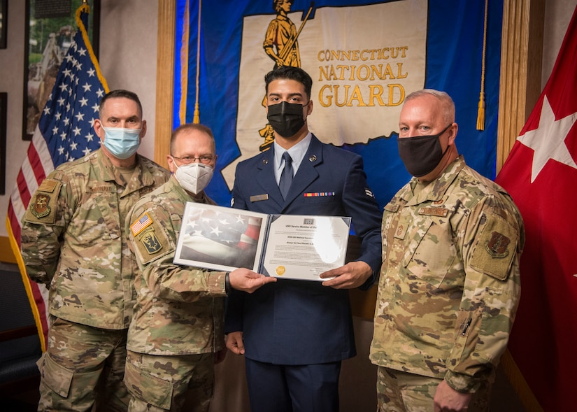 Four men in masks stand in front of a Connecticut Air National Guard flag. The middle two hold an award certificate.