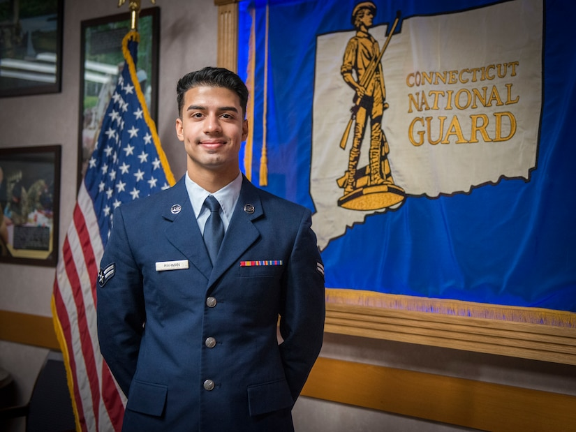 An airman stands in front of a Connecticut Air National Guard flag.