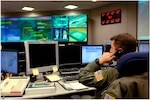 A photo of a North American Aerospace Defense Command and United States Northern Command operator answering the phone while on shift in the NORAD and USNORTHCOM command center.