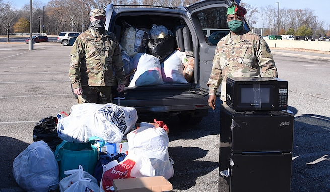 U.S. Army Space and Missile Defense Command's Sgt. 1st Class Trenton Huntsinger, noncommissioned officer in charge, G3, left, and Command Sgt. Maj. Finis Dodson, USASMDC command sergeant major, collect items for a local homeless shelter during a donation drive at the command's Redstone Arsenal, Alabama, headquarters, Dec. 18, 2020. The drive, hosted by USASMDC noncommissioned officers, collected more than 1,500 pounds of supplies to donate to the shelter. (U.S. Army photo by Mikayla Mast)