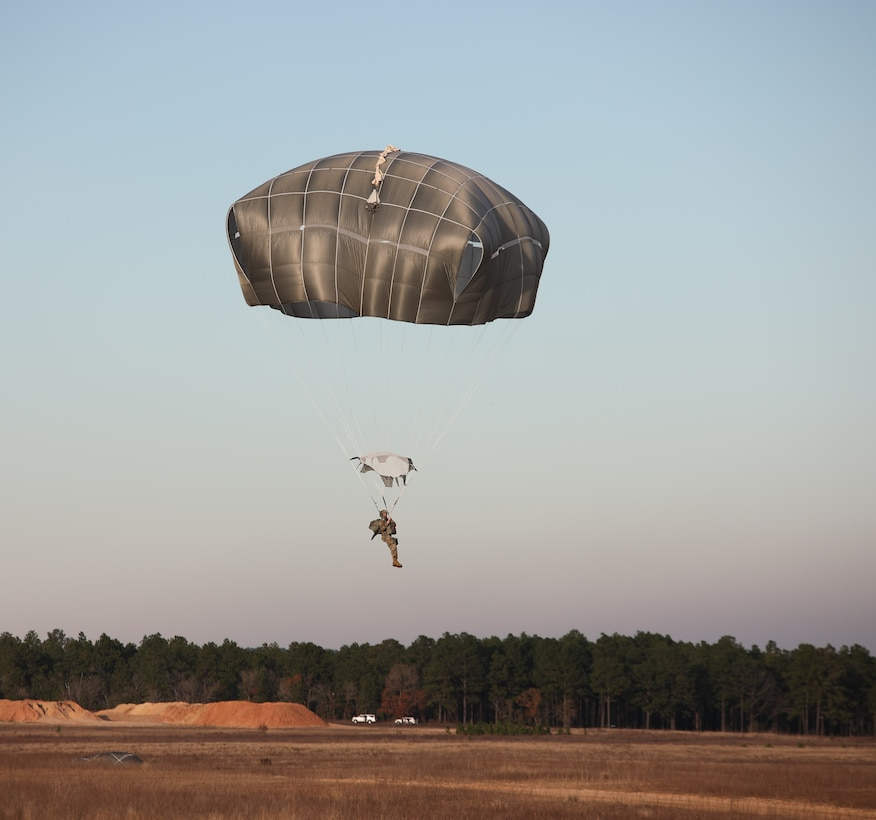 A U.S. Army paratrooper jumps from a UH-60 Black Hawk at Sicily Drop Zone, Fort Bragg, N.C., Dec. 3, 2020, during non-tactical airborne operations hosted by the U.S. Army Reserve's U.S. Army Civil Affairs and Psychological Operations Command (Airborne) and the 82nd Airborne Division.