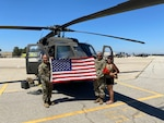 Three people stand in front of a helicopter holding an American flag