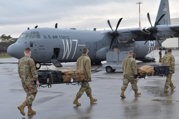 Airmen carrying supplies on stretchers toward a plane.