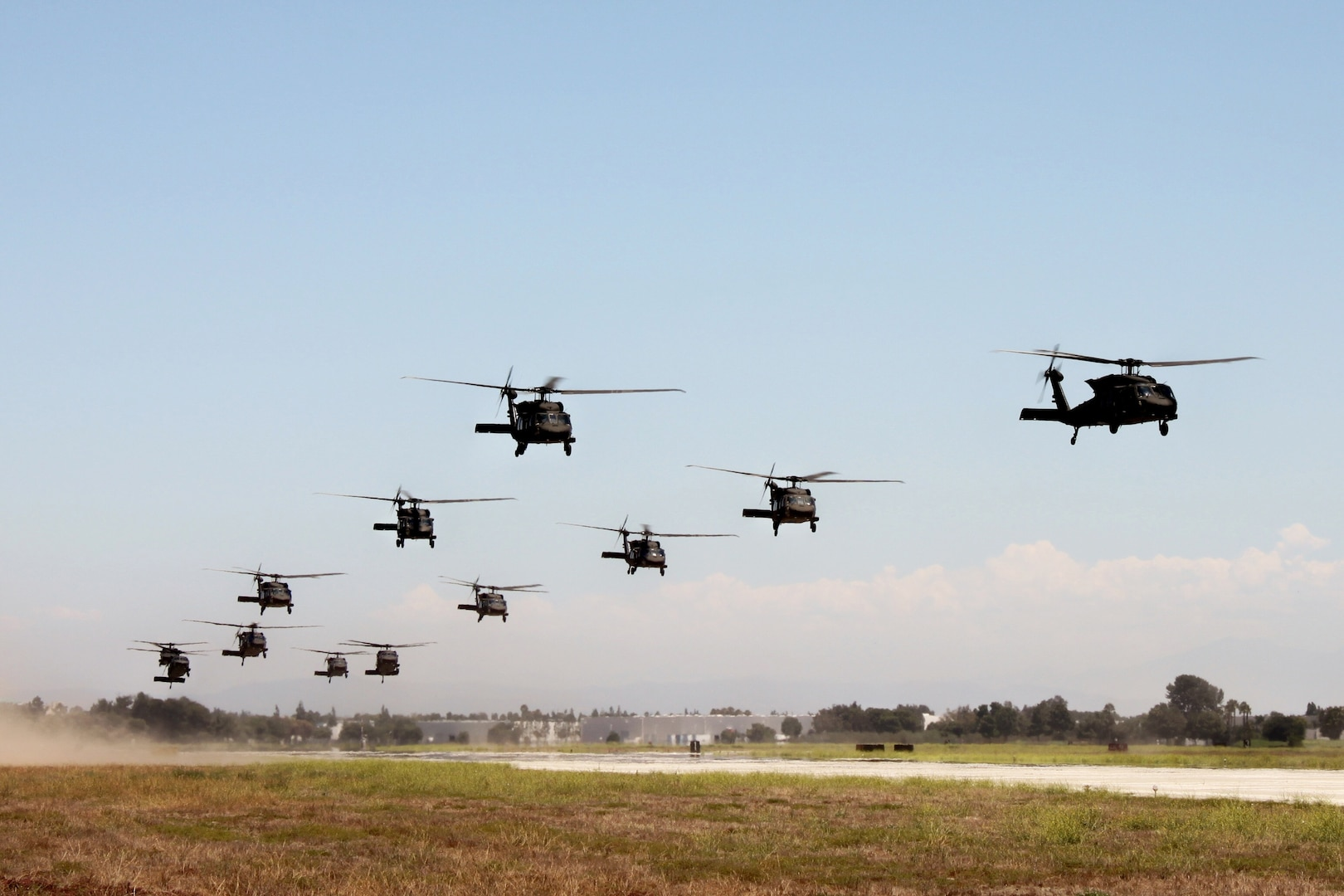 12 helicopters take off from an airfield in rapid succession.
