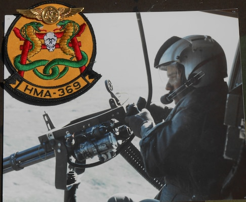 A man holds a machine gun out of the door of a helicopter