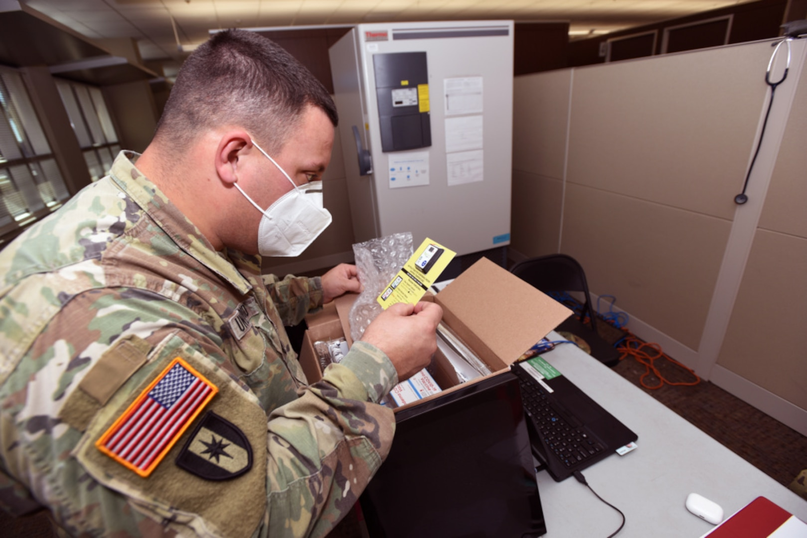 A man in operational camo pattern uniform and protective mask  unpackages a yellow card from a box.