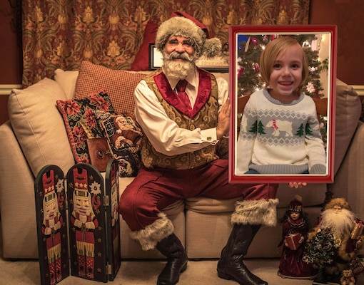 """Todd Bishop, a U.S. Army Medical Materiel Agency civilian employee, is pictured as """"Santa Todd,"""" with Evan Miller, a youngster from Homer, Ala. The virtual photo with Santa is one way Bishop has adapted to distancing requirements during the COVID-19 pandemic."""