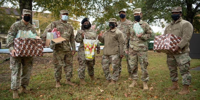 A team of master sergeants pose at the enlisted dormitories after delivering cookies to Airmen Dec. 16, 2020, on Maxwell Air Force Base, Alabama. The team wore masks and delivered the cookies in packaging to reduce the risks of COVID-19 transmission and to maintain safety.