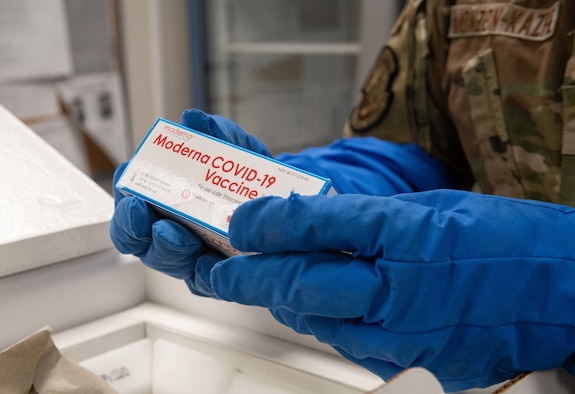 Staff Sgt. Daniel Monzon-Kazhe, 374th Medical Group non-commissioned officer in charge of contingency material, holds a box of Moderna COVID-19 vaccines
