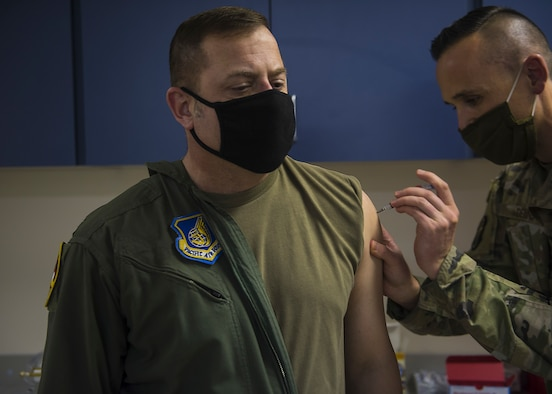 U.S. Air Force Staff Sgt. Gary Dennis, 35th Healthcare Operations Squadron NCO in charge of Allergy and Immunizations, gives Col. Jesse J. Friedel, 35th Fighter Wing commander, a dose of the COVID-19 vaccine at Misawa Air Base, Japan, Dec. 28, 2020. The Department of Defense began limited delivery of the COVID-19 vaccine to medical treatment facilities and other health care facilities for voluntary vaccination to mission essential personnel. (U.S. Air Force photo by Airman 1st Class Leon Redfern)