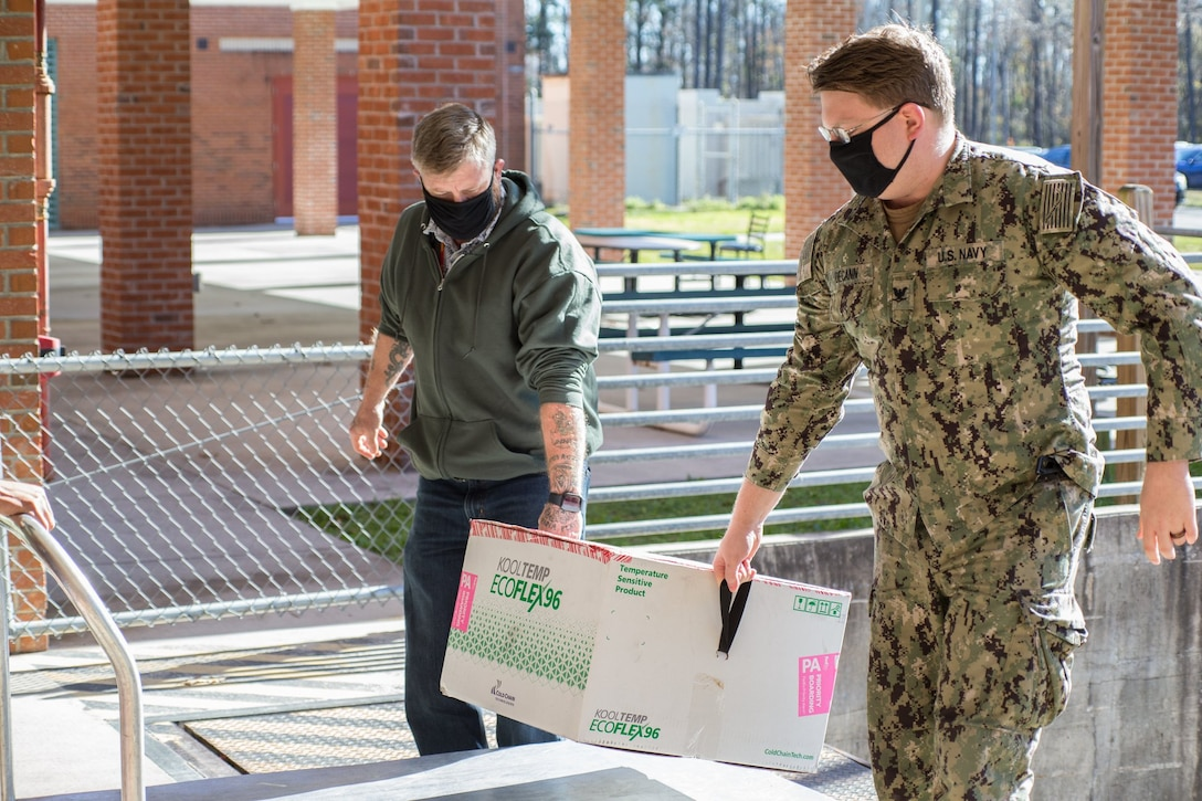 Personnel with Naval Health Clinic Cherry Point (NHCCP), North Carolina, carry in the first shipment of the Moderna COVID-19 Vaccine at Marine Corps Air Station Cherry Point, North Carolina, on Dec. 22, 2020. As with all vaccines, NHCCP will be closely following approved guidance on handling and storage of the vaccine. This vaccine will help serve as a safe and effective way to help protect our personnel and maintain mission readiness. (U.S. Marine Corps photo by Lance Cpl. Jacob Bertram)
