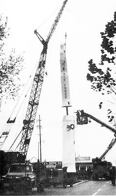 A crane places a large missile.